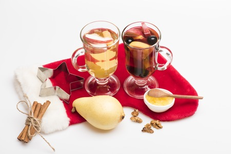 vin chaud: Two glasses of delicious glintwein or mulled red and white hot wine, cinnamon, pear, walnuts, honey, wooden spoon, silver star and Santa Claus red sock isolated on white background