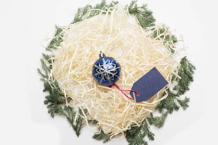 Colorful Christmas or New Year decoration with silver blue christmas ball, blue tag with rose thread and tree branch on white background