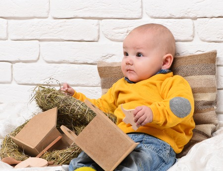leaned: small baby boy with adorable curious face in yellow sweater leaned on pillow near straw wreath with wooden elephant toy on white brick wall background