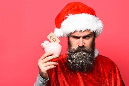 handsome bearded man with stylish mustache and long snowy beard on serious face holding pink pig piggy bank in red santa suit on studio background
