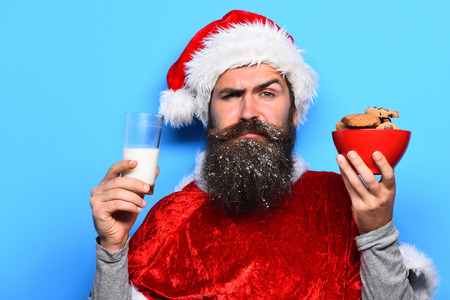 handsome bearded man with stylish mustache and long snowy beard on serious face holding glass of milk with chocolate chip cookies in red santa suit on blue studio background