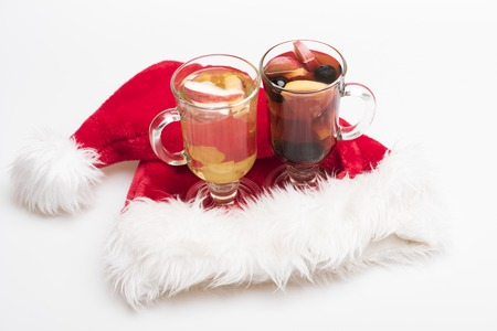 vin chaud: Two glasses of delicious glintwein or mulled red and white hot wine with Santa Claus red hat isolated on white background