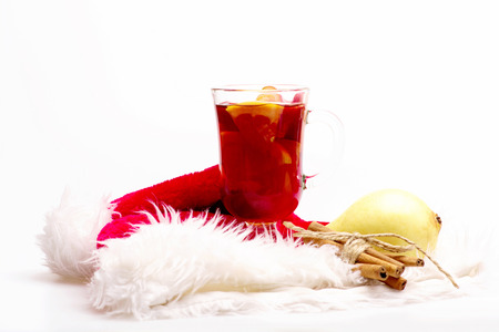 vin chaud: Glass of delicious glintwein or mulled hot wine, cinnamon and pear with Santa Claus red hat isolated on white background