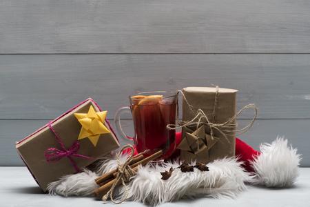 vin chaud: Un verre de délicieux glintwein ou vin chaud, de cannelle, de fil, de l'anis, des cadeaux enveloppés dans du papier kraft à l'arc avec le Père Noël chapeau rouge sur fond de bois cru Banque d'images