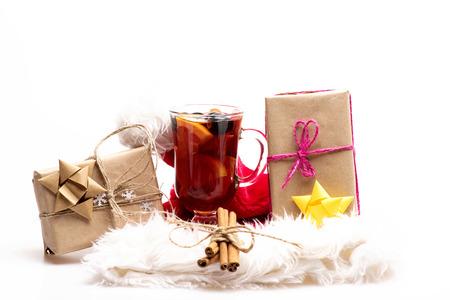 vin chaud: Un verre de délicieux glintwein ou vin chaud, la cannelle, les cadeaux enveloppés dans du papier kraft avec un arc et des flocons de neige avec le Père Noël chapeau rouge isolé sur fond blanc Banque d'images