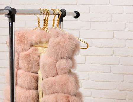 fashionable luxurious waist coat of fur hanging on rack on golden hangers on brick wall studio background