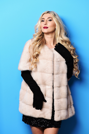 velvet dress: young fashionable   pretty woman with beautiful long curly blonde hair in waist coat of white fur and black velvet gloves on blue studio background