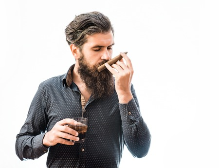 tough man: handsome bearded tough man with stylish hair mustache and long beard on serious face in blue fashion shirt sniff cigar and holding glass of whiskey isolated on white, copy space