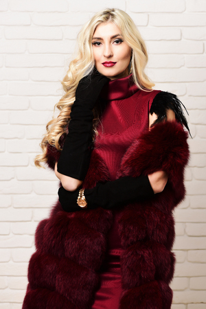 velvet dress: young fashionable   pretty woman with beautiful long curly blonde hair in waist coat of burgundy fur and dress on slim body and golden watch on black velvet gloves on brick wall studio background