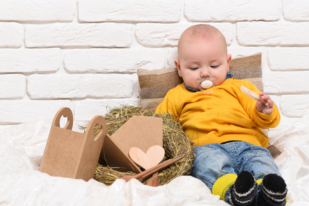 leaned: small baby boy with adorable curious face in yellow sweater and dummy leaned on pillow near straw wreath on white brick wall background Stock Photo
