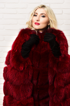 black velvet: young fashionable  pretty woman with beautiful long curly blonde hair in waist coat of burgundy or red fur and black velvet gloves on brick wall studio background