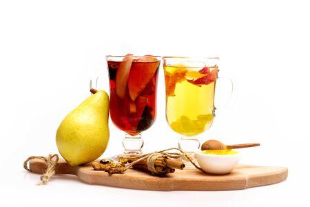 vin chaud: Deux verres de délicieux glintwein ou vin chaud chaud rouge et blanc sur une planche à découper avec un fil, la cannelle, le miel, poire, cuillère en bois et de noix isolé sur fond blanc