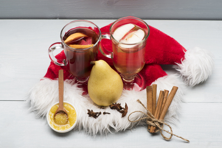 vin chaud: Two glasses of delicious glintwein or mulled red and white hot wine, cinnamon, pear, anise, honey, wooden spoon and Santa Claus red hat on vintage wooden background Banque d'images