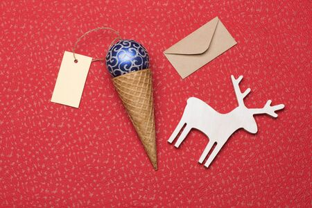 envelope decoration: Christmas or New Year decoration with blue silver christmas ball, ice cream cone, yellow tag with thread, christmas deer and envelope on red textured background