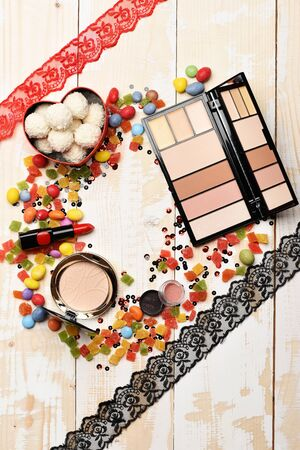 Red lipstick, cosmetic powder with white chocolate coconut candies and mix of dragee, marmalade or jelly candies, red and black ribbon on wooden background