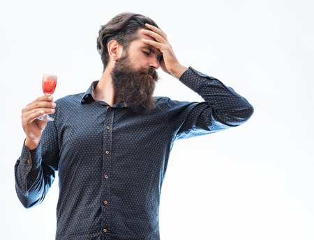 dissatisfied: handsome bearded man with stylish hair mustache and long beard on dissatisfied face holding glass of red alcoholic beverage isolated on white