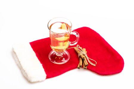 vin chaud: Un verre de délicieux glintwein ou vin chaud, la cannelle et le fil avec le Père Noël chaussette rouge isolé sur fond blanc