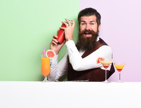 Barman, con barba y guapo con larga barba y el bigote tiene el pelo con estilo en la cara divertida que sostiene agitador y Alcohol en el chaleco de gamuza de cuero de la vendimia en el fondo del estudio púrpura verde Foto de archivo - 68971673