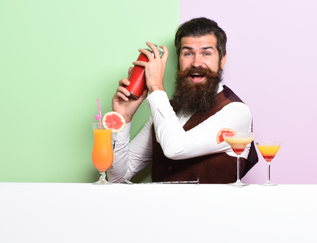 handsome bearded barman with long beard and mustache has stylish hair on funny face holding shaker and made alcoholic cocktail in vintage suede leather waistcoat on purple green studio background Stockfoto
