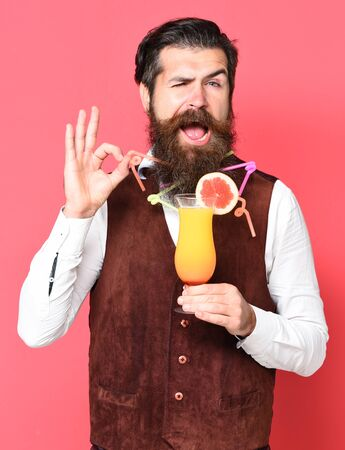 handsome bearded man with colorful tubes in long beard and mustache has stylish hair on funny face holding glass of alcoholic cocktail in vintage suede leather waistcoat on red studio background