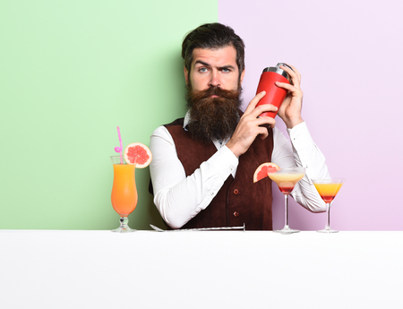 handsome bearded barman with long beard and mustache has stylish hair on serious face holding shaker and made alcoholic cocktail in vintage suede leather waistcoat on purple green studio background Foto de archivo