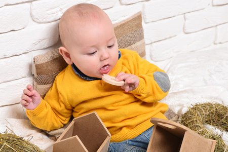 leaned: small baby boy with adorable curious face in yellow sweater leaned on pillow and playing with wooden box on white brick wall background