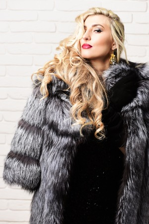 young fashionable sexy pretty rich woman with beautiful long curly blonde hair in waist coat of grey fur and dress with black velvet gloves on brick wall studio background