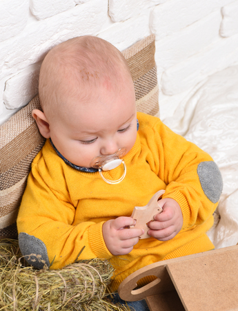 leaned: small baby boy with adorable curious face in yellow sweater leaned on pillow and playing with wooden elephant toy on white brick wall background