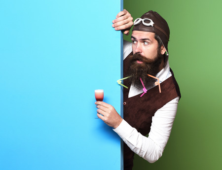 handsome bearded pilot man with long beard and mustache on surprised face holding glass of alcoholic shot in vintage suede leather waistcoat with hat and glasses on blue green studio background Stock Photo