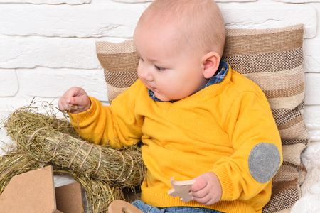 leaned: small baby boy with adorable curious face in yellow sweater leaned on pillow and playing with straw wreath on white brick wall background