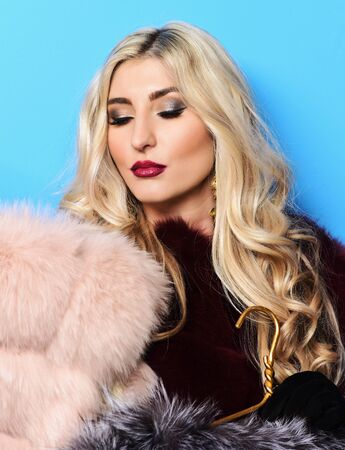 young fashionable sexy pretty woman with beautiful long curly blonde hair and fashion makeup holding grey and beige fur coat on blue studio background Stock Photo
