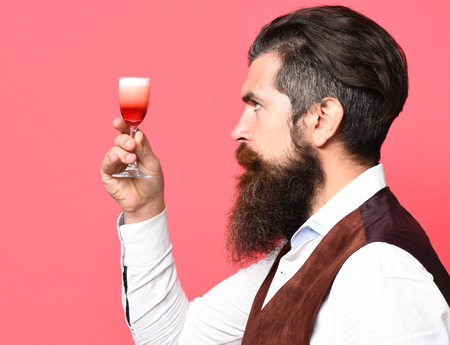 handsome bearded man with long beard and mustache has stylish hair on serious face holding glass of alcoholic shot in vintage suede leather waistcoat on red studio background