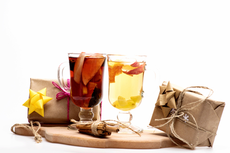 vin chaud: Two glasses of delicious glintwein or mulled red and white hot wine on cutting board with thread, cinnamon and gifts wrapped in craft paper with bow and snowflakes isolated on white background Banque d'images