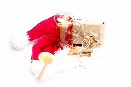 wine gift: Glass of delicious glintwein or mulled hot wine, gift wrapped in craft paper with bow, snowflakes, cinnamon, honey, wooden spoon and Santa Claus red hat isolated on white background Stock Photo