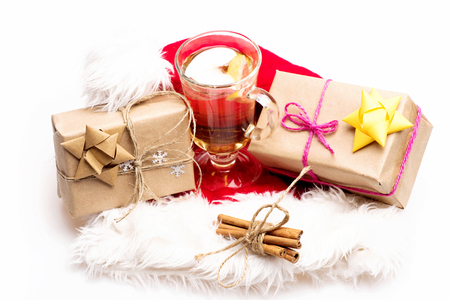vin chaud: Glass of delicious glintwein or mulled hot wine, cinnamon, gifts wrapped in craft paper with bow and snowflakes with Santa Claus red hat isolated on white background Banque d'images