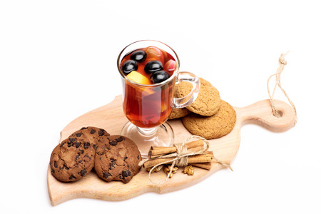 Glass of delicious glintwein or mulled hot wine on cutting board with thread, cinnamon, walnuts and oatmeal cookies isolated on white background