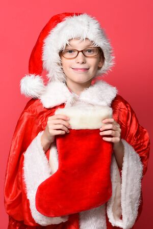 young cute santa claus boy with glasses in red sweater and new year hat holds decorative christmas or xmas stocking or boot on studio background