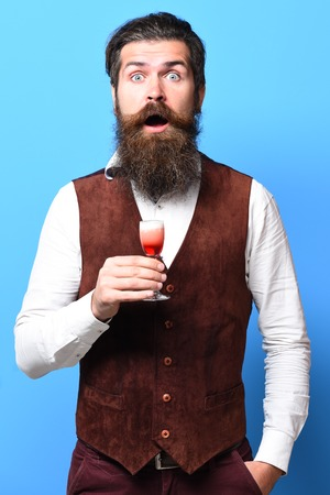 handsome bearded man with long beard and mustache on surprised face tasting glass of alcoholic shot in vintage suede leather waistcoat on blue studio background
