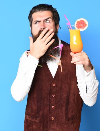 handsome bearded man with colorful tubes in long beard and mustache has stylish hair on surprised face holding glass of alcoholic cocktail in vintage suede leather waistcoat on blue studio background