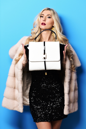 young fashionable sexy pretty woman with beautiful long curly blonde hair in waist coat of beige fur showing white black fashion bag on blue studio background Stock Photo