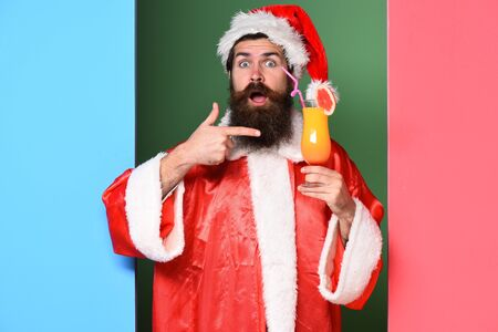 handsome bearded santa claus man with long beard on surprised face holding glass of nonalcoholic cocktail in christmas or xmas sweater and new year hat shows on it on colorful studio background Stock Photo