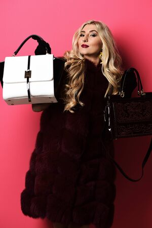 young fashionable sexy pretty woman with beautiful long curly blonde hair in waist coat of burgundy fur and black velvet gloves showing fashion bags on red studio background