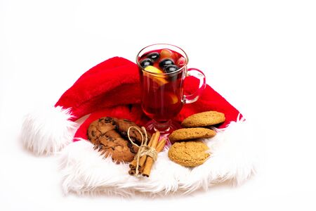 vin chaud: Glass of delicious glintwein or mulled hot wine, cinnamon and oatmeal cookies with Santa Claus red hat isolated on white background