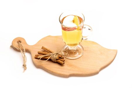 vin chaud: Glass of delicious glintwein or mulled hot wine on cutting board with thread, cinnamon isolated on white background
