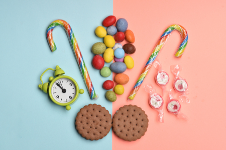 12 oclock: Chocolate pastry, colorful dragee with raisins or peanuts inside, striped caramel candies, sugar candies and green alarm clock on colorful background