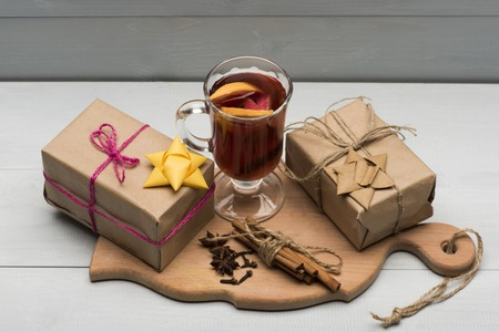 vin chaud: Glass of delicious glintwein or mulled hot wine, cinnamon, thread, anise and gifts wrapped in craft paper with bow on vintage wooden background