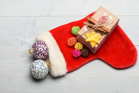Colorful Christmas or New Year decoration include gift with rose string, yellow bow, cinnamon, Santa Claus red sock, purple white balls, colorful clews and snowflakes on vintage wooden background