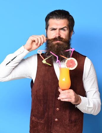 handsome bearded man with colorful tubes in long beard and mustache has stylish hair on serious face holding glass of alcoholic cocktail in vintage suede leather waistcoat on blue studio background Stock Photo