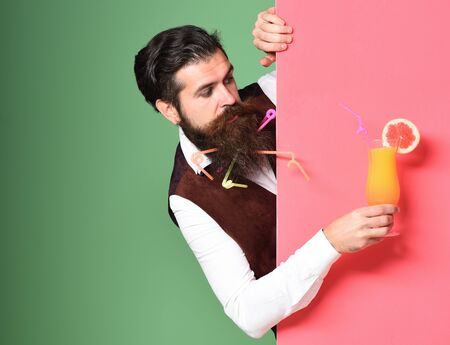 handsome bearded man with in long beard and mustache has stylish hair on serious face holding glass of alcoholic cocktail in vintage suede leather waistcoat on colorful studio background