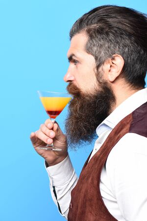 handsome bearded man with long beard and mustache has stylish hair on serious face tasting glass of alcoholic cocktail in vintage suede leather waistcoat on blue studio background